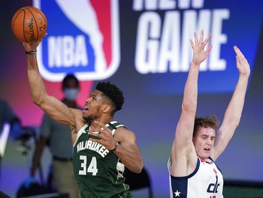 Pebasket Milwaukee Bucks, Giannis Antetokounmpo, berusaha memasukkan bola saat melawan Washington Wizards pada laga NBA, Selasa (11/8/2020). Bucks mengalahkan Wizards dengan skor 126-113. (AP Photo/Ashley Landis, Pool)