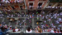 Orang-orang berlari menghindari serudukan banteng selama hari ketiga Festival San Fermin di Pamplona, Spanyol utara, (9/7). Ratusan orang dari seluruh dunia  setiap tahunnya ambil bagian dalam Festival Adu Banteng, San Fermin. (AP Photo/Alvaro Barrientos)