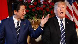 Presiden AS, Donald Trump dan PM Jepang Shinzo Abe berbincang selama pertemuan di Resor Mar-a-Lago, Florida, Selasa (17/4). Pertemuan mengangkat isu-isu lain seperti perdagangan, dan hubungan diplomatik dengan China. (AP/Pablo Martinez Monsivais)