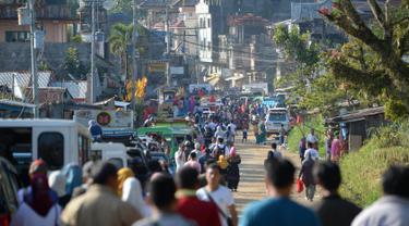 Ribuan orang berjalan memasuki Kota Marawi, Mindanao, Filipina, Minggu (1/4). Pihak berwenang mengizinkan warga mengunjungi rumah mereka yang hancur di area pertempuran militer Filipina dengan militan ISIS. (TED ALJIBE/AFP)