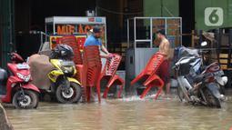 Pedagang membersihkan bangku di Kawasan pertokoan Jalan KH Hasyim Ashari, Ciledug, Tangerang, Kamis (2/1/2020). Banjir yang melanda Ciledug dan sekitarnya membuat aktivitas perekonomian di kawasan tersebut lumpuh sementara. (Liputan6.com/Angga Yuniar)