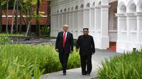 Momen ketika Presiden AS Donald Trump (kiri) dengan Pemimpin Korea Utara Kim Jong-un berjalan di taman Hotel Capella, Pulau Sentosa, Singapura, Selasa (12/6). Trump dan Kim optimis bahwa KTT akan sukses. (Anthony Wallace/Pool/AFP)