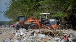 Pekerja menggunakan alat berat membersihkan sampah dan sampah plastik saat pembersihan pantai Kuta dekat Denpasar di pulau wisata Bali (6/1/2021). Tiga alat berat dikerahkan untuk memudahkan pengangkutan sampah. (AFP/Sonny Tumbelaka)