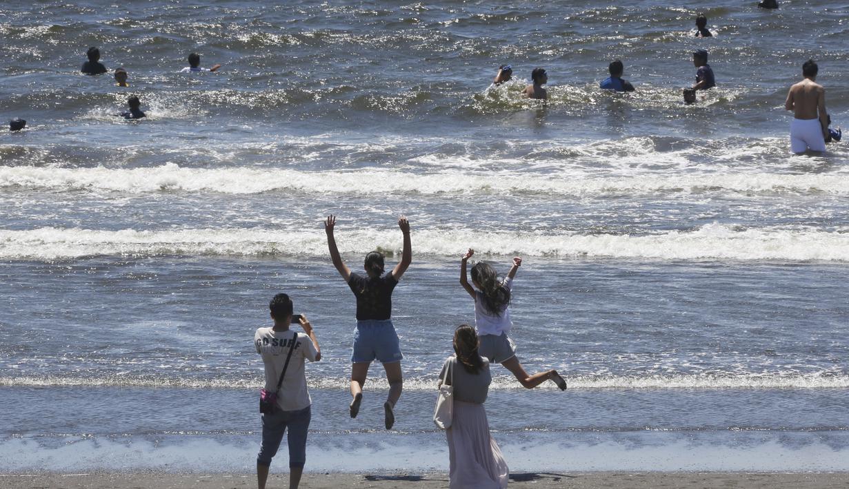 Orang-orang menikmati Pantai Shonan untuk menyejukkan diri dari teriknya musim panas di Fujisawa, dekat Tokyo, Selasa, (11/8/2020). (AP / Koji Sasahara)
