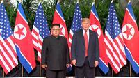Presiden AS Donald Trump dan Pemimpin Korea Utara, Kim Jong-un berpose sebelum pertemuan mereka di resor Capella, Pulau Sentosa, Selasa (12/6). Pertemuan Trump  dan Kim sudah banyak dinantikan dunia. (Host Broadcaster Mediacorp Pte Ltd via AP)