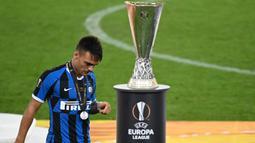 Pemain Inter Milan, Lautaro Martinez, berjalan melewati trofi Liga Europa 2019/2020 di Stadion RheinEenergie, Sabtu (22/8/2020) dini hari WIB. Inter Milan kalah 2-3 atas Sevilla. (AFP/Ina Fassbender/pool)
