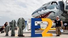 Pengunjung berfoto dengan latar belakang pesawat Embraer E190-E2 yang ditampilkan di Farnborough Airshow, London, Inggris, Kamis (19/7. Farnborough Airshow memamerkan pesawat model terbaru. (Adrian DENNIS/AFP)