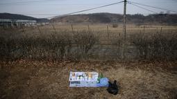 """Sebuah persembahan untuk kerabat dan leluhur warga asal Korea Utara diletakkan di depan kawat berdiri pada Tahun Baru Imlek di """"desa harapan"""" Imjingak, dekat zona demiliterisasi yang memisahkan kedua Korea di Paju, Selasa (5/2). (Ed JONES/AFP)"""