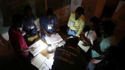 Para petugas menghitung jumlah suara di sebuah Tempat Pengumutan Suara (TPS) di Port-au-Prince, Haiti (20/11). Akibat badai Matthew yang sebelumnya melanda kota ini, pemilu harus digelar dengan penerangan seadanya. (Reuters/Jeanty Junior Augustin)
