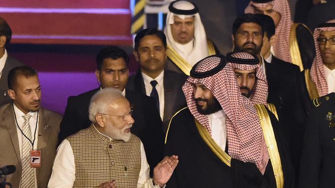 PM India, Narendra Modi menyambut kedatangan Putra Mahkota Arab Saudi Pangeran Mohammed bin Salman di bandara New Delhi, Selasa (19/2). Rencananya pembicaraan kerja sama bilateral akan dilakukan Modi dan Pangeran MBS pada Rabu (20/2). (Money SHARMA/AFP)
