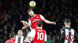 Bek Arsenal, Shkodran Mustafi, menyundul bola saat melawan Newcastle United pada laga Premier League di Stadion Emirates, Minggu (16/2/2020). Arsenal menang 4-0 atas Newcastle United. (AP/Frank Augstein)