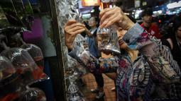Seorang wanita melihat ikan untuk dijual di Mong Kok Goldfish Market, distrik Kowloon, Hong Kong pada 10 November 2018. Pedagang menggantung ikan hias di dalam plastik bening sehingga pengunjung bisa memilih sendiri ikan yang dimau. (VIVEK PRAKASH/AFP)