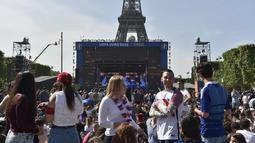 Sejumlah warga berkumpul di sekitar layar raksasa yang terdapat pada acara Champs de Mars yang digelar untuk menyambut Piala Eropa 2016 di Paris fan zone, belakang Menara Eiffel, Prancis, Jumat (10/6/2016). (AFP/Alain Jocard)