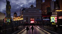 Orang-orang berjalan di sepanjang Las Vegas Strip yang sepi setelah perintah penutupan kasino akibat virus corona COVID-19, Las Vegas, Amerika Serikat, Rabu (18/3/2020). Selain kasino, bioskop, bar, restoran, dan pusat kebugaran juga ditutup. (AP Photo/John Locher)