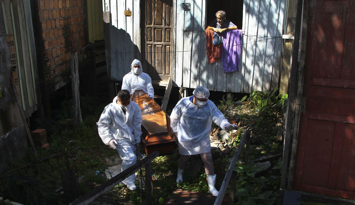 Anggota keluarga menyaksikan petugas pemakaman mengeluarkan jenazah Amelia Dias Nascimento (94) yang meninggal akibat komplikasi COVID-19 di rumahnya, di Manaus, negara bagian Amazonas (22/1/2021). Jumlah orang meninggal di rumah di tengah pandemi meningkat di Brasil. (AP Photo/Edmar Barros)