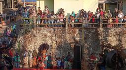 Warga menyaksikan aksi tarian kuda lumping para penari komunitas lima gunung di Desa Mantran Wetan, Kabupaten Magelang, Jumat  (11/10/2019). Pertunjukan ini bagian dari Perayaan Saparan sebagai wujud syukur warga di desa itu. (Liputan6.com/Gholib)
