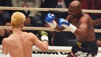Petinju, Floyd Mayweather, berusaha memukul kickboxer, Tenshin Nasukawa, pada laga eksebisi di Saitama Super Arena, Saitama, Senin (31/1). Tanding dengan aturan tinju, Mayweather menang TKO di ronde pertama. (AFP/Toshifumi Kitamura)