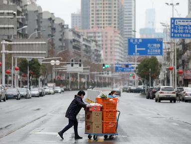 Warga membawa makanan dan sayuran di Wuhan di provinsi Hubei tengah China (3/3/2020). Hingga saat ini, jumlah total kasus virus corona secara global dilaporkan mencapai 89.770 kasus yang tersebar di sekitar 70 negara termasuk Indonesia. (AFP/STR)