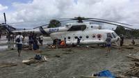 Warga berusaha menggali lumpur yang menimbun helikopter Mi-17 milik BNPB pasca banjir bandang di Kabupaten Sentani, Jayapura, (17/3). Banjir bandang Sentani menewaskan 70 orang dan puluhan luka-luka. (AFP/Netty Dharma Somba)