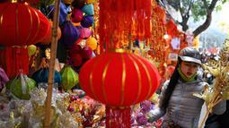 Seorang wanita berbelanja dekorasi Tahun Baru Imlek atau perayaan Tet di sebuah pasar pusat Kota Tua Hanoi, Senin (28/1). Setiap perayaan imlek, warga Vietnam akan menghias rumah dengan berbagai dekorasi berwarna merah. (Manan VATSYAYANA/AFP)