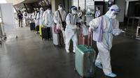 Penumpang asing yang mengenakan pakaian pelindung berjalan untuk penerbangan mereka ke China di Bandara Internasional Manila, Filipina, Senin (18/1/2021). Infeksi virus corona COVID-19 di Filipina telah melonjak melewati 500 ribu kasus.  (AP Photo/Aaron Favila)