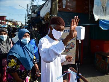 Seorang pria mengukur suhu tubuhnya sebelum memasuki pasar untuk membeli makanan, sebagai bagian dari upaya untuk menghentikan penyebaran virus corona Covid-19, selama bulan suci Ramadhan di provinsi selatan Thailand, Narathiwat (17/4/2021). (AFP/Madaree Tohlala)