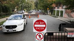 Kendaraan pasukan Secret Service terparkir di ujung jalan menuju rumah mantan Presiden AS, Barack Obama di Washington, Rabu (24/10). Dinas Rahasia AS menggagalkan pengiriman paket berisi bahan peledak ke rumah Obama. (CHIP SOMODEVILLA/GETTY IMAGES/AFP)