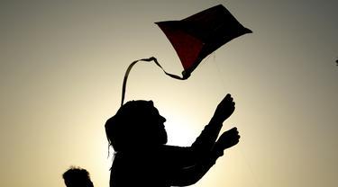 Seorang wanita saat menerbangkan layang-layang di festival layang-layang tahunan di Baghdad, Irak (5/6/2021). Festival layang-layang diadakan menarik ratusan penduduk setempat untuk menerbangkan layang-layang. (Xinhua/Khalil Dawood)