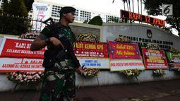 Tentara bersenjata  berjaga dekat karangan bunga yang ada di Gedung Komisi Pemilihan Umum (KPU), Jakarta, Sabtu (20/4). Karangan bunga terus berdatangan ke Gedung KPU. (merdeka.com/Imam Buhori)