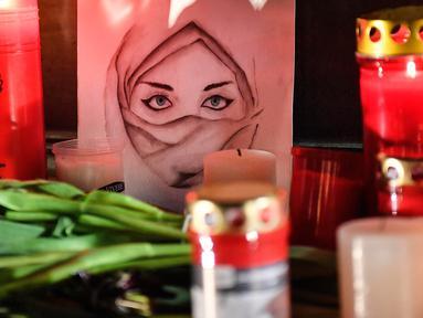 Gambar seorang wanita terlihat di antara lilin dan bunga saat berkabung untuk para korban penembakan brutal di Hanau, Jerman, Kamis (20/2/2020). Penembakan yang terjadi di dua bar shisha Kota Hanau menewaskan sembilan orang dan melukai sejumlah orang lainnya. (AP Photo/Martin Meissner)