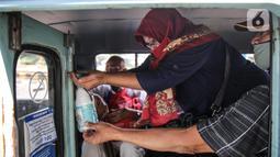 Penumpang menggunakan cairan pembersih tangan saat menaiki angkutan umum Jak Lingko di kawasan Cawang, Jakarta, Senin (6/7/2020). Pada perpanjangan masa PSBB transisi, angkutan umum sudah mulai beroperasi kembali dengan menerapkan protokol Kesehatan Covid-19. (Liputan6.com/Faizal Fanani)