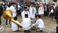 Tim Tanjidor beristirahat di tengah kerumunan saat Festival Lebaran Betawi IX di Lapangan Banteng, Jakarta, Minggu (14/8). Lebaran Betawi mulai diselenggarakan tahun 2008 dan terus ada hingga kini. (Liputan6.com/Immanuel Antonius)