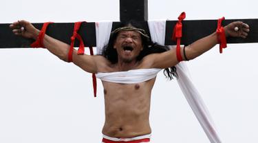 Ruben Enaje merintih ketika tangannya dipaku ke tiang salib di Pampanga, Filipina, Jumat (30/3). Aksi tersebut dilakukan dalam rangka visualisasi penderitaan Yesus Kristus menyambut Jumat Agung. (AP Photo/Aaron Favila)