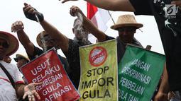 Perwakilan petani tebu menebarkan gula rafinasi saat berunjuk rasa di sekitar depan Istana Negara, Jakarta, Selasa (16/10). Mereka menuntut pemerintah menyetop impor gula karena dinilai merugikan petani. (Liputan6.com/Helmi Fithriansyah)