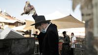 Seorang pria Yahudi ultra-Ortodoks mengayunkan ayam di atas kepalanya sebagai bagian dari ritual Kaparot di Yerusalem, Rabu (23/9/2020). Sebagian percaya, ritual Kaparot akan membebaskan mereka dari dosa-dosa yang ditransfer ke ayang yang dipotong.  (AP Photo/Maya Alleruzzo)