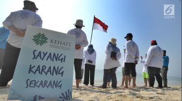 Aktivis Yayasan Kehati Jakarta  dan penjaga pulau melakukan upacara bendera menghadap laut dalam rangka HUT ke-74 RI di Pulau Sangiang, Banten, Minggu (18/8/2019). Kegiatan ini dilakukan serentak secara nasional di 73 titik untuk mencintai laut dan sumber daya alamnya. (merdeka.com/Arie Basuki)