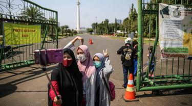Sejumlah warga berswafoto di depan kawasan Monumen Nasional (Monas), Jakarta, Minggu (26/7/2020). Sejumlah warga mulai mengunjungi kawasan Monas meski masih ditutup sementara di masa PSBB transisi. (Liputan6.com/Faizal Fanani)