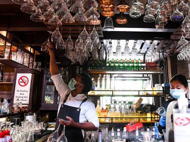 Bartender Gagan (kiri) dan seorang pelayan membersihkan bar jelang pembukaan kembali di New Delhi, 8 September 2020. Setelah sebelumnya ditutup karena pandemi COVID-19, mulai 9 September 2020 New Delhi mengizinkan bar kembali buka dengan kapasitas tempat duduk 50 persen. (Prakash SINGH/AFP)