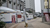 Petugas mengenakan APD saat menyemprotkan disinfektan di luar zona merah RSD Wisma Atlet, Kemayoran, Jakarta, Senin (23/11/2020). Total kasus konfirmasi COVID-19 di Indonesia hari ini mencapai angka 502.110 usai penambahan harian sebanyak 4.442. (merdeka.com/Iqbal S Nugroho)