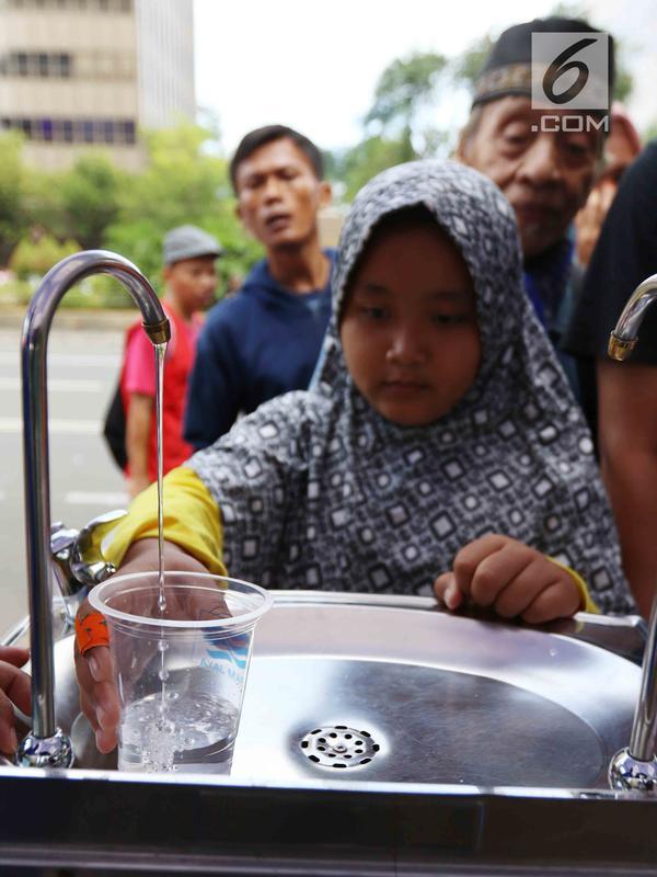 Seorang anak mengambil air minum gratis saat run for water di CFD, Jakarta, Minggu (25/3). Run For Water kolaborasi PAM Jaya, Palyja, dan Aetra mengkampanyekan Hari Air Dunia 2018 mengajak masyarakat ayo peduli air Jakarta. (Liputan6.com/Angga Yuniar)