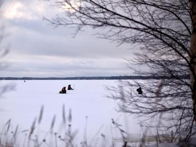 Sejumlah pria memancing di tengah laut Bothnia yang sedang membeku di Vaasa, Finlandia, Rabu (27/12). Memancing di laut beku merupakan hal yang ditunggu-tunggu oleh sebagian warga setempat. (OLIVIER MORIN / AFP)