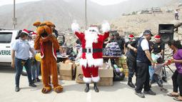 Seorang polisi Peru berpakaian seperti Santa Claus berteriak untuk memberikan hadiah kepada warga selama perayaan Natal di Huaycan, Lima, Peru (15/12/2015). (REUTERS/Janine Costa)