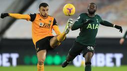 Gelandang Wolverhampton Wanderers, Roman Saiss (kiri), berebut bola dengan gelandang Tottenham Hotspur, Tanguy Ndombele, dalam laga lanjutan Liga Inggris 2020/21 pekan ke-15 di Molineux Stadium, Minggu (27/12/2020). Wolherhampton bermain imbang 1-1 dengan Spurs. (AFP/Lindsey Parnaby/Pool)