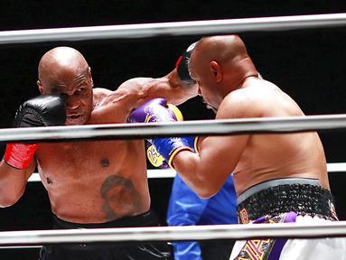 Mike Tyson melakukan pukulan terhadap Roy Jones Jr pada pertarungan tinju eksibisi di Los Angeles, Amerika Serikat, Sabtu (28/11/2020). Pertandingan berakhir tanpa pemenang alias imbang. (Joe Scarnici/Triller via AP)