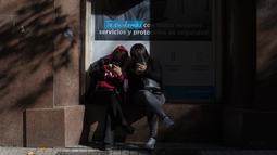 Para perempuan melihat ponsel mereka saat menunggu di kantor layanan kesehatan di pusat kota Santiago, Sabtu (12/6/2021). Ibu kota Chile mengembalikan tindakan karantina di tengah meningkatnya kasus COVID-19, meskipun hampir 60% warga negara itu sudah divaksinasi sepenuhnya. (AP Photo/Esteban Felix)