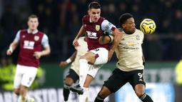 Penyerang Manchester United, Anthony Martial, berebut bola dengan pemain Burnley, Ashley Westwood, pada laga Premier League di Stadion Turf Moor, Sabtu (28/12). Burnley takluk 0-2 dari Manchester United. (AP/Martin Rickett)