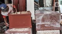 Pekerja menyelesaikan pembuatan peti jenazah untuk pasien Covid-19 di TPU Pondok Kelapa, Jakarta, Selasa (13/7/2021). Menurut pekerja, dalam sehari mampu membuat hingga 50 peti jenazah dari ratusan pesanan dari pihak rumah sakit, baik di Jakarta maupun luar kota. (merdeka.com/Iqbal S Nugroho)