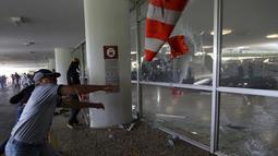 Anggota polisi memecahkan jendela saat mencoba masuk ke Gedung Kongres Nasional Brasil selama unjuk rasa, Brasilia (18/4). RUU yang diusulkan oleh Presiden Brasil Michel Temer ini menetapkan usia pensiun polisi adalah 65 tahun. (AP Photo / Eraldo Peres)