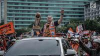 Ketua PP The Jakmania Ferry Indrasjarief membawa Piala Presiden yang diraih oleh Persija Jakarta pada pawai kemenangan di kawasan Sudirman, Minggu (18/2). Tak ada pengalihan arus di sepanjang jalur konvoi Persija dan Jakmania. (Liputan6.com/Faizal Fanani)