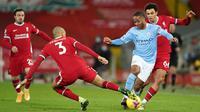 Gelandang Manchester City, Raheem Sterling (tengah) dikepung dua pemain Liverpool, Fabinho (kiri) dan Trent Alexander-Arnold dalam laga lanjutan Liga Inggris 2020/21 pekan ke-23 di Anfield Stadium, Minggu (7/2/2021). Manchester City menang 4-1 atas Liverpool. (AFP/Jon Super/Pool)
